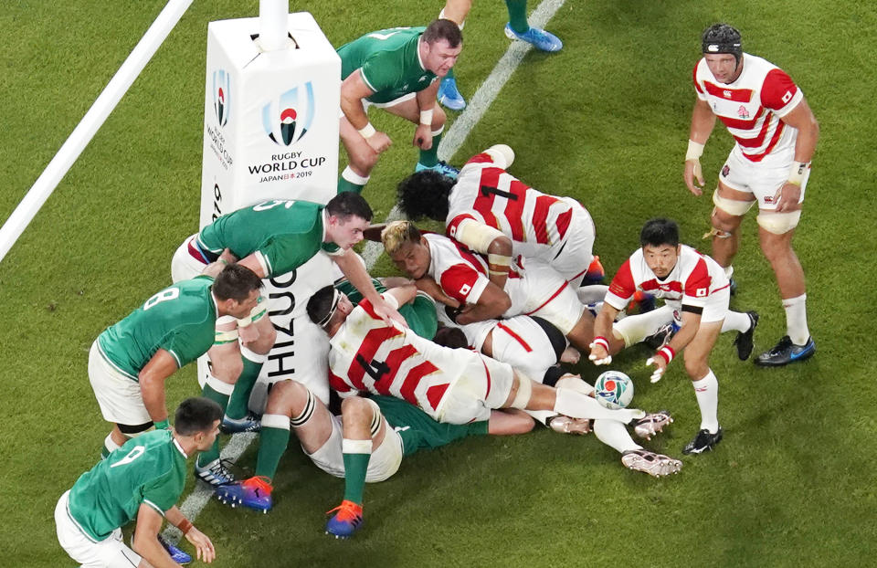 Japan's Fumiaki Tanaka, second right, passes the ball against Ireland's defense during the Rugby World Cup Pool A game at Shizuoka Stadium Ecopa between Japan and Ireland in Shizuoka, Japan, Saturday, Sept. 28, 2019. (Kyodo News via AP)
