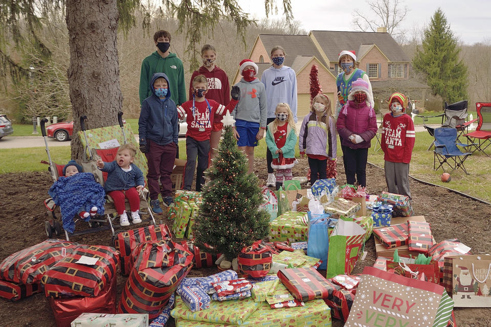 In this Dec. 23, 2020, photo provided by courtesy of George Peters, the Peters family outdoor socially-distanced Christmas exchange is held on the front lawn at Renee and Dan Schauer's home in Cincinnati. Left to right are the grandchildren of Joe and Nancy Peters: Taylor J. and Oliva Meade in strollers; front row, Jane Matthews, Ben Felblinger, Amelia Hoying, Abby Felblinger, Maggie Hoying and Zach Felblinger; back row, Brad Schauer, Sarah Schauer, Nate Hoying, Ellie Schauer and Grandma Nancy Peters. The pandemic and its isolating restrictions have been especially tough for many of the nation's some 70 million grandparents, many at ages when they are considered most vulnerable to the deadly COVID-19 virus. (George Peters via AP)