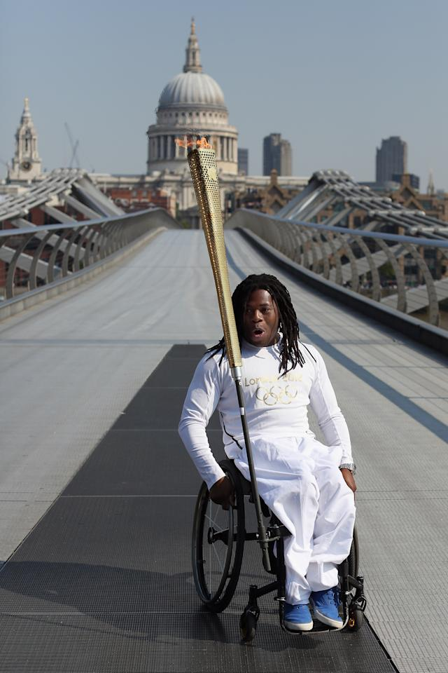 LONDON, ENGLAND - JULY 26:  Wheelchair basketball player Adedoyin Adepitan carries the Olympic flame over Millennium Bridge in front of St Paul's Cathedral during Day 69 of the London 2012 Olympic Torch Relay on July 26, 2012  in London, England. The Olympic flame is making its way through the capital on the penultimate day of its journey around the UK before arriving in the Olympic Stadium on Friday evening for the Olympic games' Opening Ceremony.  (Photo by Oli Scarff/Getty Images)