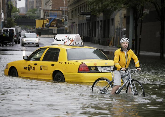 FILE - In this Aug. 28, 2011, file photo, a biker makes his way around a taxi stranded in floodwaters of Hurricane Irene, downgraded to a tropical storm, in New York. Two years before Irene created the prospect of a flooding nightmare in New York City, 100 scientists and engineers met to sketch out a bold defense: massive, moveable barriers to shield the city from a storm-stirred sea.(AP Photo/Peter Morgan, File)