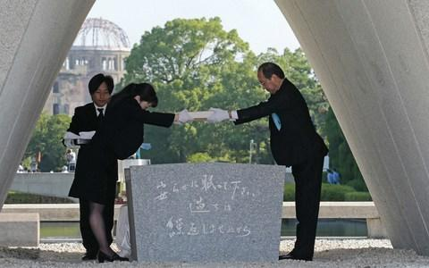 Hiroshima Mayor Kazumi Matsui (R) offers a new list of A-bomb dead, including individuals who died since last year's anniversary from the side effects of radiation - Credit: AFP