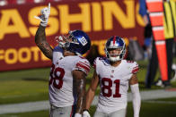 New York Giants tight end Evan Engram (88) pointing upwards after scoring a touchdown against the Washington Football Team, Sunday, Nov. 8, 2020, in Landover, Md. Also on the field is teammate wide receiver Austin Mack (81). (AP Photo/Susan Walsh)
