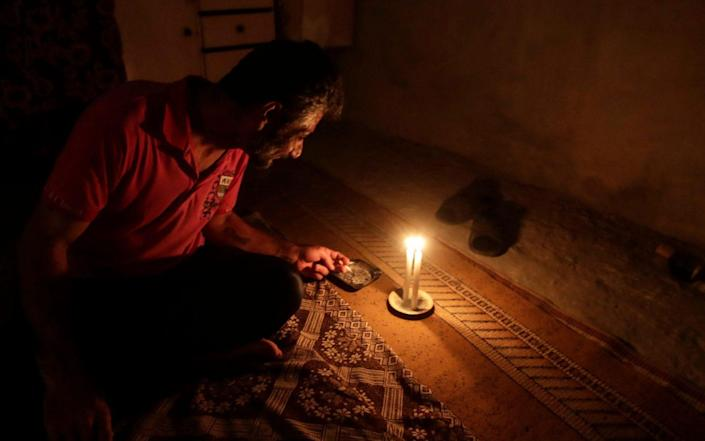 A Lebanese man smokes a cigarette by candlelight in the capital Beirut on July 10, 2021 - ANWAR AMRO/AFP