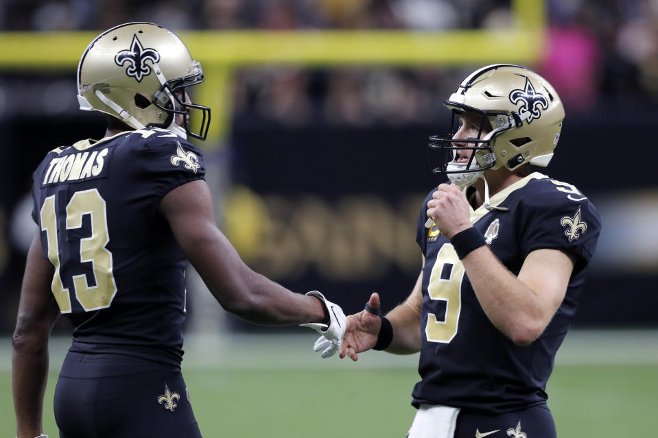 New Orleans Saints quarterback Drew Brees (9) greets wide receiver Michael Thomas (13) after a touchdown. (AP Photo/Bill Feig)
