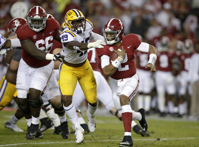 Alabama quarterback Jalen Hurts carries the ball before being tackled by LSU linebacker Arden Key during the first half of an NCAA college football game, Saturday, Nov. 4, 2017, in Tuscaloosa, Ala. (AP Photo/Brynn Anderson)