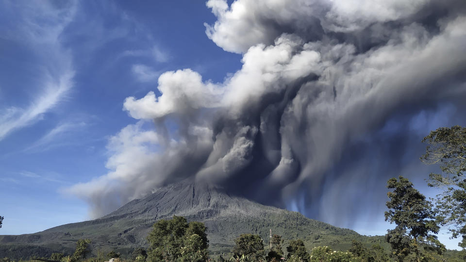 "Mount Sinabung spews volcanic materials during an eruption, in Karo, North Sumatra, Indonesia, Sunday, Aug. 23, 2020. Sinabung is among more than 120 active volcanoes in Indonesia, which is prone to seismic upheaval due to its location on the Pacific ""Ring of Fire,"" an arc of volcanoes and fault lines encircling the Pacific Basin. (AP Photo)"