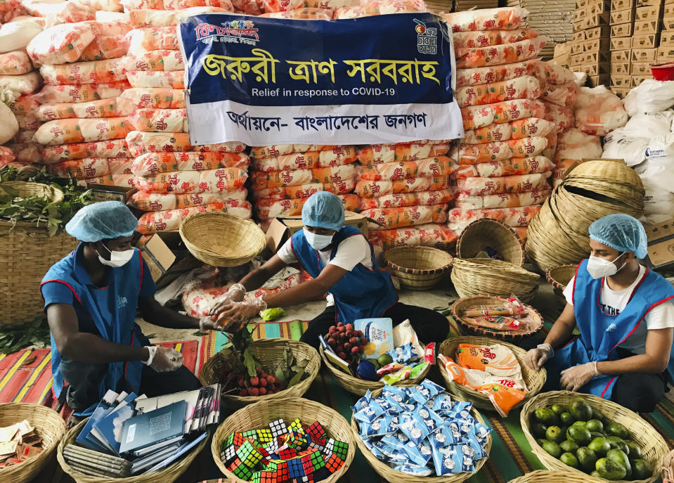 FILE - In this June 6, 2020, file photo, members of Bidyanondo Foundation volunteers pack care packages for COVID-19 patients in Dhaka, Bangladesh. A new snapshot of the frantic global response to the coronavirus pandemic shows some of the world's largest government donors of humanitarian assistance are buckling under the strain and overall aid commitments have dropped by a third from the same period last year. (AP Photo/Al-emrun Garjon, File)