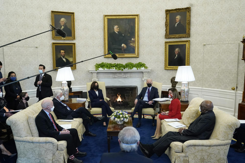 President Joe Biden, accompanied by Vice President Kamala Harris, speaks with House Speaker Nancy Pelosi and House Majority Whip James Clyburn, right, House Majority Leader Steny Hoyer, seated second left, and Rep. Peter DeFazio, D-Or., seated left, and Rep. John Yarmuth, D-Ky., foreground, in the Oval Office of the White House, Friday, Feb. 5, 2021, in Washington. (AP Photo/Alex Brandon)