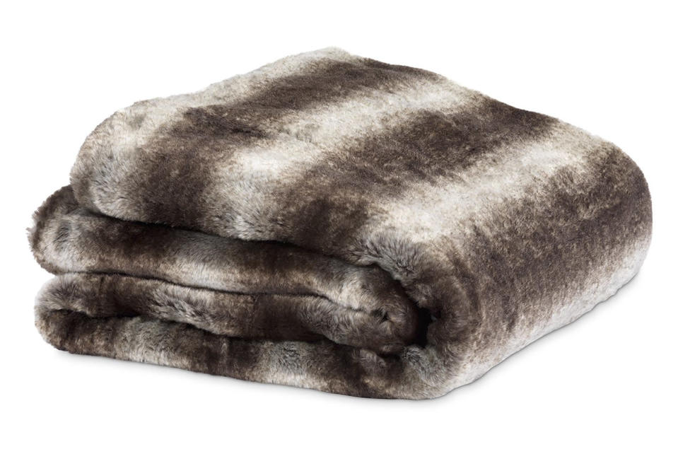This image provided by HomeGoods shows a faux fur blanket. Marcy Blum, a NY-based wedding and event planner and HomeGoods style expert, suggests filling a basket with throws and pillows for guests who will be gathering outdoors during your Noon Year's Eve bash. (HomeGoods via AP)