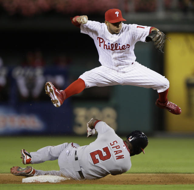 Philadelphia Phillies shortstop Freddy Galvis, top, leaps over Washington Nationals' Denard Span after forcing him out at second base on a ball hit by Bryce Harper, who was safe at first during the third inning of a baseball game, Tuesday, Sept. 3, 2013, in Philadelphia. (AP Photo/Matt Slocum)