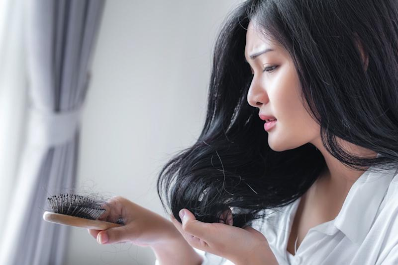 Attractive Asian woman serious about her brush for presentation hair loss problem and looking at comb.