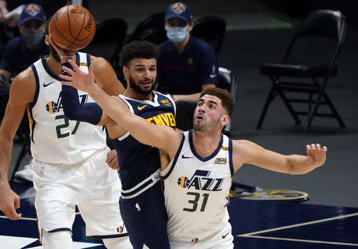 Utah Jazz forward Georges Niang, right, fouls Denver Nuggets guard Jamal Murray, center, while pursuing the ball in the first half of an NBA basketball game Sunday, Jan. 17, 2021, in Denver. (AP Photo/David Zalubowski)