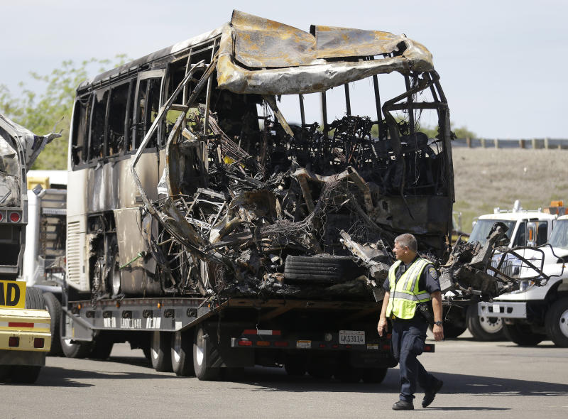 A California Highway Patrol officer walks past the charred remains of a tour bus at a CalTrans maintenance station in Willows, Calif., Friday, April 11, 2014. At least ten people were killed and dozens injured in the fiery crash on Thursday, April 10, between a FedEx truck and a bus carrying high school students on a visit to a Northern California college. (AP Photo/Jeff Chiu)