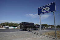 """A U.S. Customs and Border Protection vehicle, left, and a truck pulls a trailer near a sign welcoming motorists to Del Rio, Texas, near the Del Rio International Bridge, which remains closed due to a migrant encampment alongside the bridge, Friday, Sept. 24, 2021, in Del Rio, Texas. The """"amistad,"""" or friendship, that Del Rio, Texas, and Ciudad Acuña, Mexico, celebrate with a festival each year has been important in helping them deal with the challenges from a migrant camp that shut down the border bridge between the two communities for more than a week. (AP Photo/Julio Cortez)"""