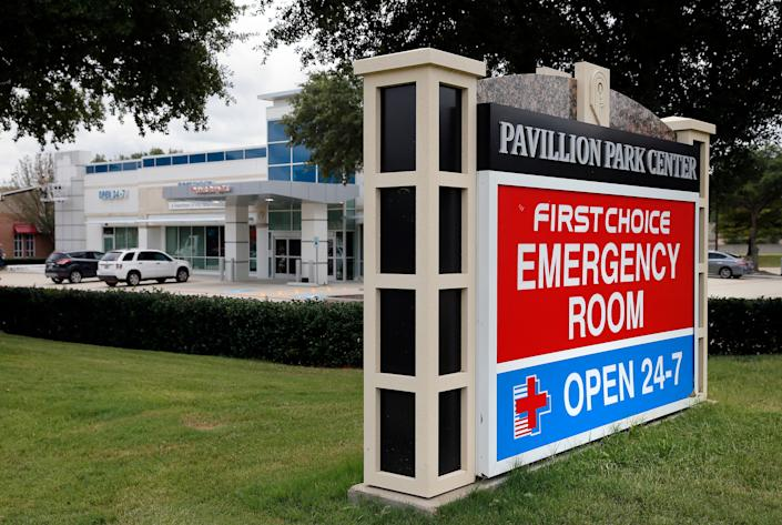 A sign by a nearby road intersection advertises a First Choice Emergency Room, rear, Thursday, Aug. 18, 2016, in Richardson, Texas.