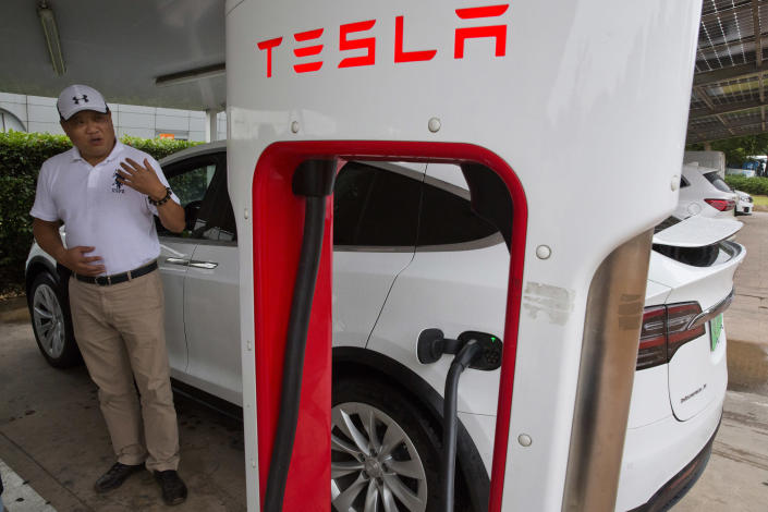 In this June 22, 2018, photo, Shan Junhua chats about privacy near his white Tesla while charging it in Shanghai. When Shan bought his white Tesla Model X, he knew it was a fast, beautiful car. What he didn't know is that Tesla constantly sends information about the precise location of his car to the Chinese government. Automakers selling electric vehicles in China send a constant feed of information about the location of cars to the government, potentially adding to the rich kit of surveillance tools available to the regime as President Xi Jinping steps up the use of technology to track Chinese citizens. (AP Photo/Ng Han Guan)