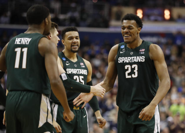 Michigan State forward Xavier Tillman (23) celebrates with teammates after scoring against Duke during the second half of an NCAA men's East Regional final college basketball game in Washington, Sunday, March 31, 2019. (AP Photo/Patrick Semansky)