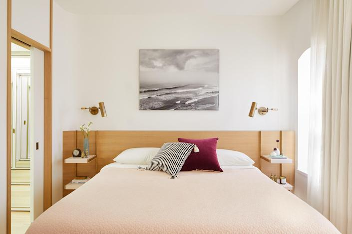 In the primary bedroom, the headboard is custom white oak with end tables wrapped in pink leather and hanging with brass rods.