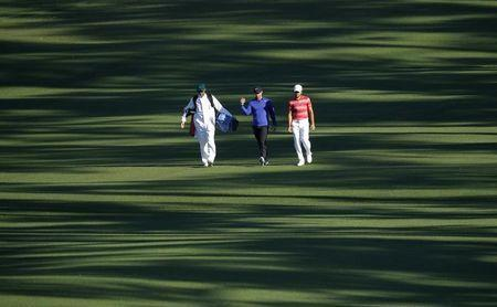 Rory McIlroy of Northern Ireland (C) walks up the second fairway with Toto Gana of Chile (R) during Tuesday practice rounds for the 2017 Masters at Augusta National Golf Course in Augusta, Georgia, U.S., April 4, 2017. REUTERS/Mike Segar