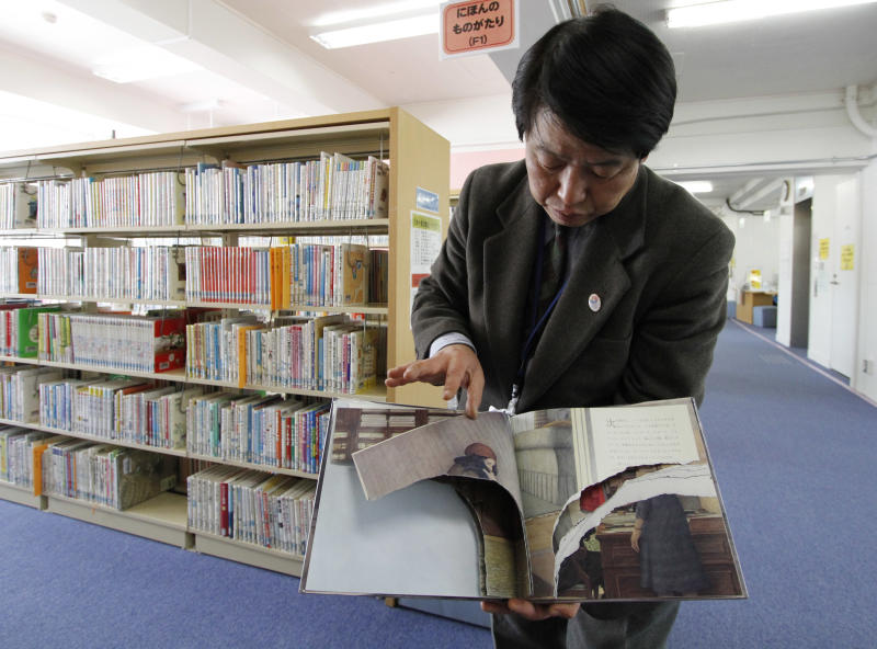 """A ripped copy of Anne Frank's """"Diary of a Young Girl"""" picture book is shown by Shinjuku City Library Director Kotaro Fujimaki at the library in Tokyo Friday, Feb. 21, 2014. Tokyo Libraries said on Friday that hundreds of copies of Anne Frank's diary and related books have been found vandalised across the city's libraries in the last month, sparking fears of an anti-Semitic motive. A total of 265 books in 31 libraries had been found damaged after the first damaged book was found in January, prompting a wider search. (AP Photo/Koji Ueda)"""