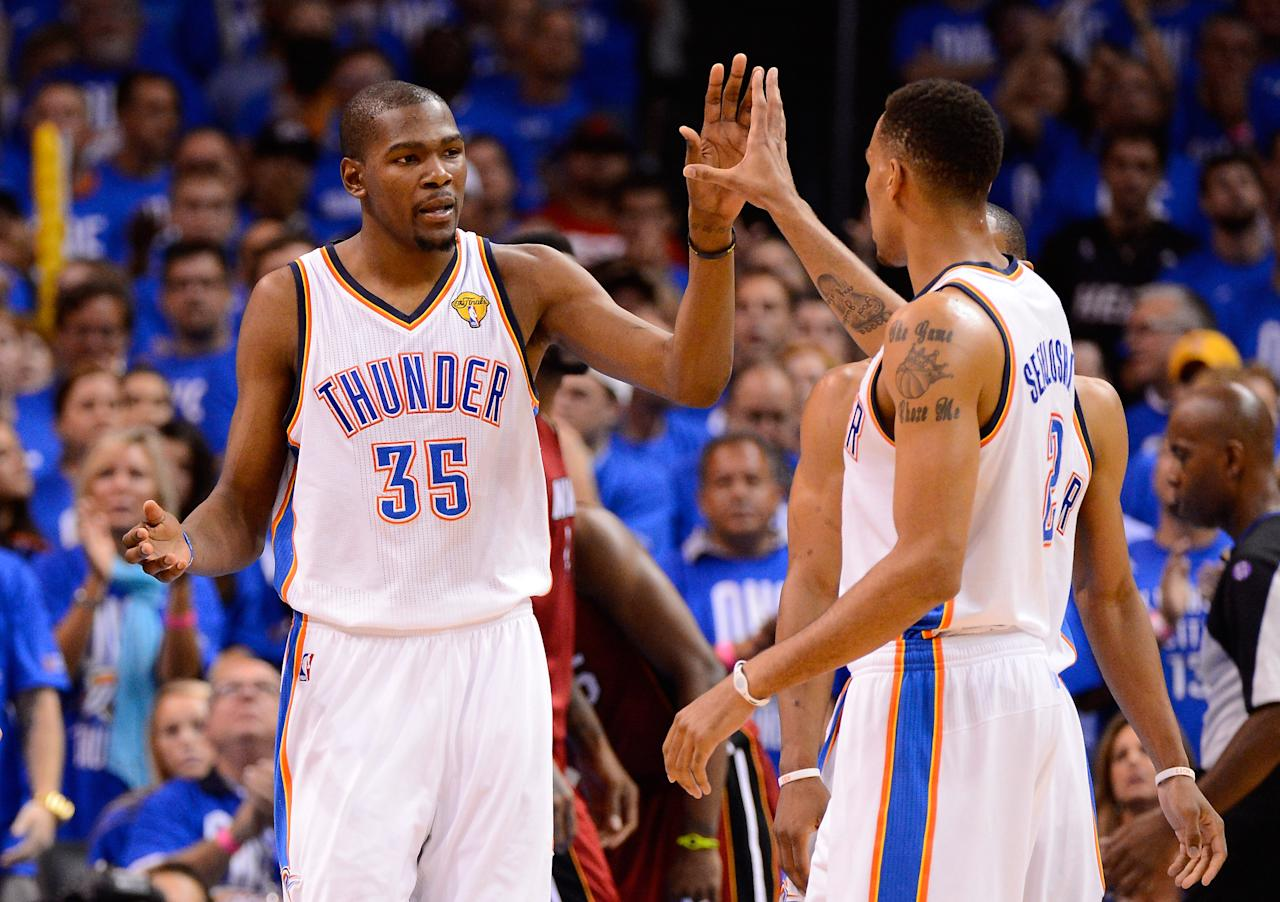 OKLAHOMA CITY, OK - JUNE 12:  Kevin Durant #35 and Thabo Sefolosha #2 of the Oklahoma City Thunder give each other a high five in the third quarter in Game One of the 2012 NBA Finals at Chesapeake Energy Arena on June 12, 2012 in Oklahoma City, Oklahoma. NOTE TO USER: User expressly acknowledges and agrees that, by downloading and or using this photograph, User is consenting to the terms and conditions of the Getty Images License Agreement.  (Photo by Ronald Martinez/Getty Images)