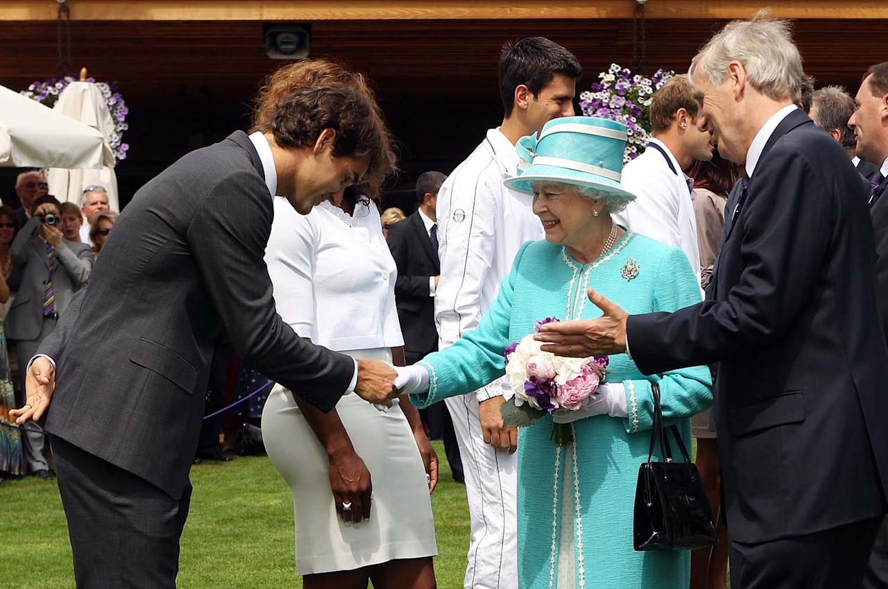 Britain's Queen Elizabeth II  meets defending champion Roger Federer as she attends the Wimbledon Lawn Tennis Championships .for the first time in 33 years, Thursday June 24, 2010.(AP Photo/Oli Scarff, pool)