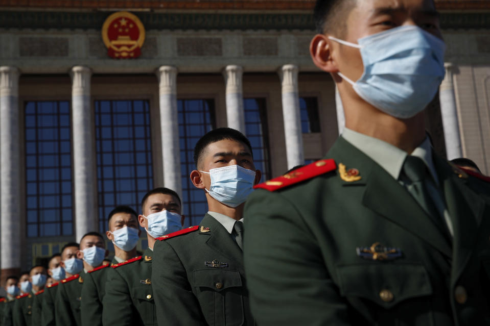 Chinese paramilitary policemen wearing face masks to help curb the spread of the coronavirus march outside the Great Hall of the People after attending the commemorating conference on the 70th anniversary of China's entry into the 1950-53 Korean War, in Beijing Friday, Oct. 23, 2020. (AP Photo/Andy Wong)