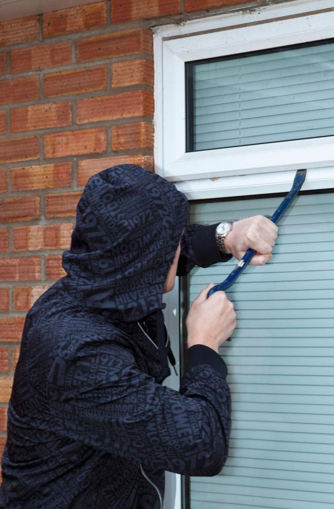 A man tries to force open a window on a house.