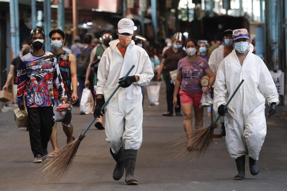 Workers wearing protective suits walks beside residents at a public market during the start of a stricter lockdown to help prevent the spread of the coronavirus in Marikina city, Philippines on Monday, March 29, 2021. Philippine officials placed Metropolitan Manila and four outlying provinces, a region of more than 25 million people, back to a lockdown Monday at the height of the Lenten and Easter holiday travel season as they scrambled to control an alarming surge in coronavirus infections. The Department of Health reported more than 10,000 new COVID-19 cases Monday, the highest since the pandemic hit the country. (AP Photo/Aaron Favila)