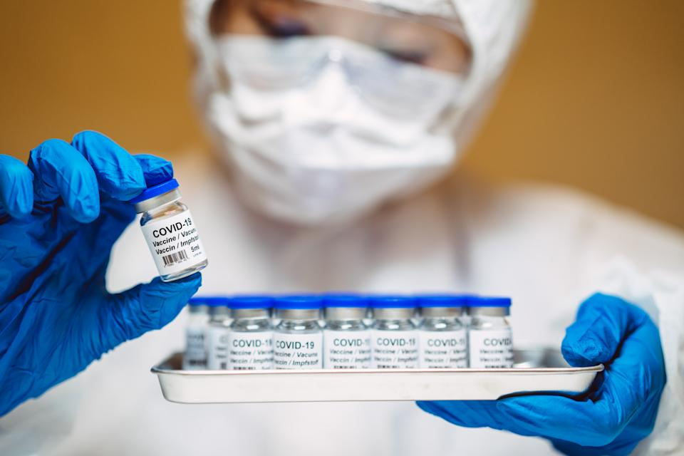 Healthcare professional in protective gloves & workwear holding & organising a tray of COVID-19 vaccine vials. The professional is carrying out researches on COVID-19 vaccine in laboratory.