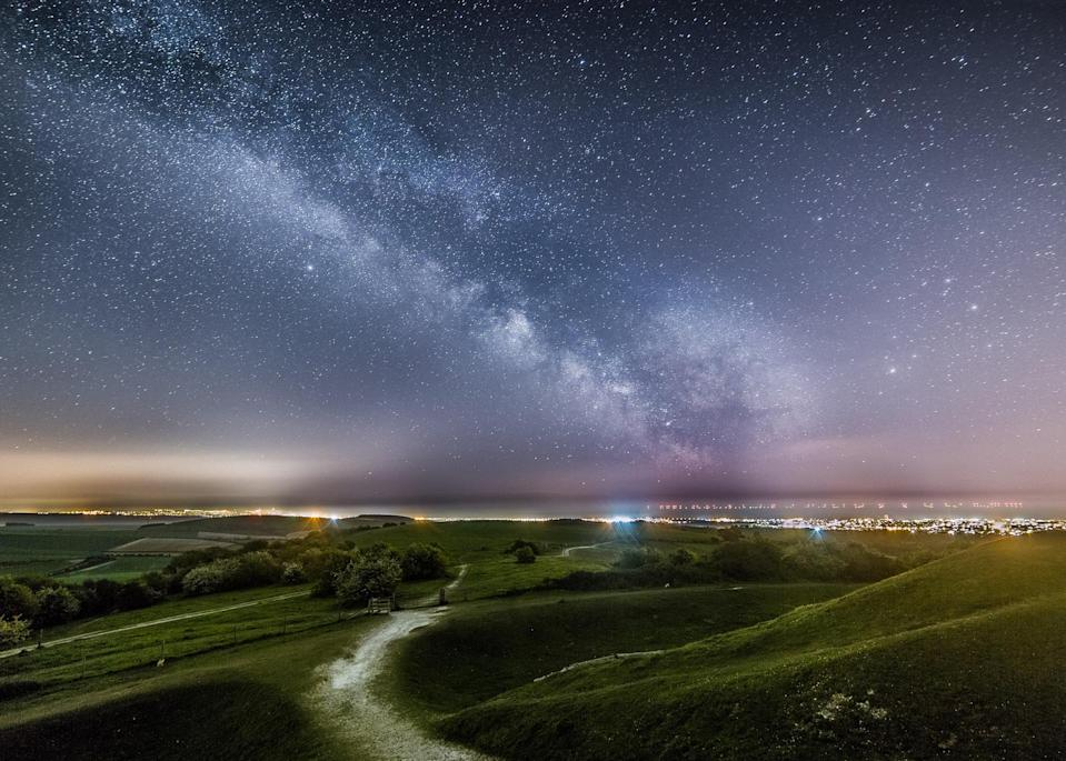 The Milky Way above the lights of Worthing and Brighton from Cissbury Ring with the lights of the Rampion Wind farm in the background by Neil Jones (Neil Jones/PA)