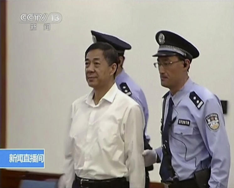 In this image taken from video, disgraced politician Bo Xilai, center, enters a courtroom flanked by police guards at Jinan Intermediate People's Court in eastern China's Shandong province on Thursday, Aug. 22, 2013. Bo went on trial Thursday accused of abuse of power and netting more than $4 million in bribery and embezzlement, marking the ruling Communist Party's attempts to put to rest one of China's most lurid political scandals in decades. (AP Photo/CCTV via AP Video)