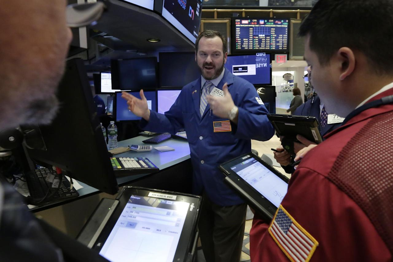 Specialist Charles Boeddinghaus, center works at his post on the floor of the New York Stock Exchange, Tuesday, Jan. 17, 2017. Stocks are opening slightly lower on Wall Street, led by declines in banks and health care companies. (AP Photo/Richard Drew)