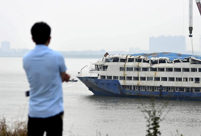 "A man looks at the Eastern Star cruise ship being towed to a safer area, after it capsized in the Jianli section of the Yangtze River, in Huarong county, Hunan province, China, June 10, 2015. The ship was moved to another area on Wednesday, 10 kilometres from where it sank, to escape from the rapid currents, local media reported. Chinese investigators looking into last week's deadly capsizing of a packed cruise ship have collected a ""multitude of first-hand evidence"" and have interviewed many people including the captain, state media said on Wednesday. Picture taken June 10, 2015. REUTERS/China Daily CHINA OUT. NO COMMERCIAL OR EDITORIAL SALES IN CHINA"