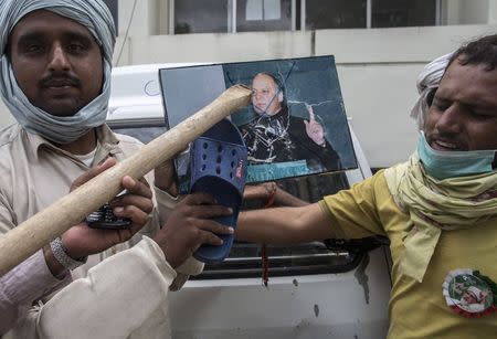 Supporters of Tahir ul-Qadri, a Sufi cleric and leader of Pakistan Awami Tehreek (PAT) party, use a sandal to hit a defaced portrait of Prime Minister Nawaz Sharif, as a sign of disrespect, after storming the building of the state television channel PTV, during the Revolution March in Islamabad September 1, 2014. REUTERS/Zohra Bensemra