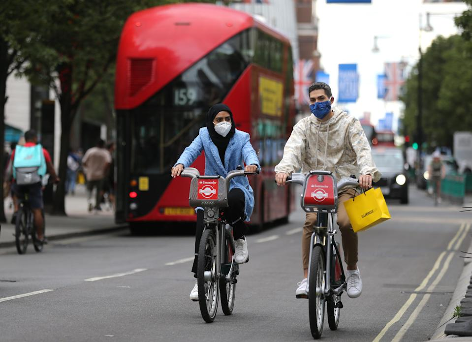 Shoppers cycle on Santander bikes on Oxford Street, London, as non-essential shops in England open their doors to customers for the first time since coronavirus lockdown restrictions were imposed in March. Picture date: Monday June 15, 2020.