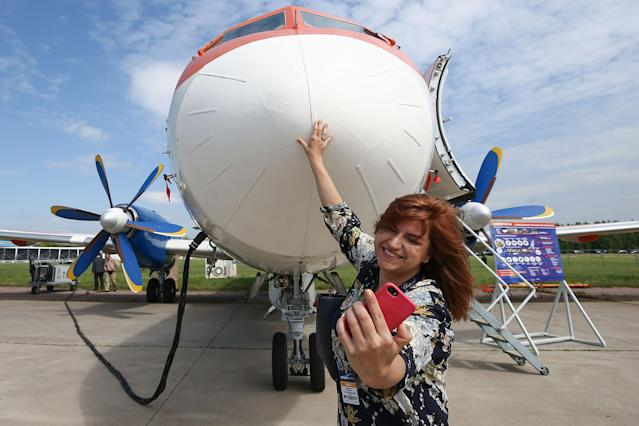 <p>A visitor takes a selfie with an Ilyushin Il-114 twin-engine turboprop airliner on display at the MAKS-2017 International Aviation and Space Salon in Zhukovsky, Moscow Region, Russia, July 18, 2017. (Photo: Sergei Bobylev/TASS via Getty Images) </p>