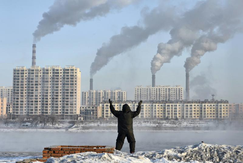 File photo of a man exercising in the morning as he faces chimneys emitting smoke behind buildings across the Songhua river in Jilin