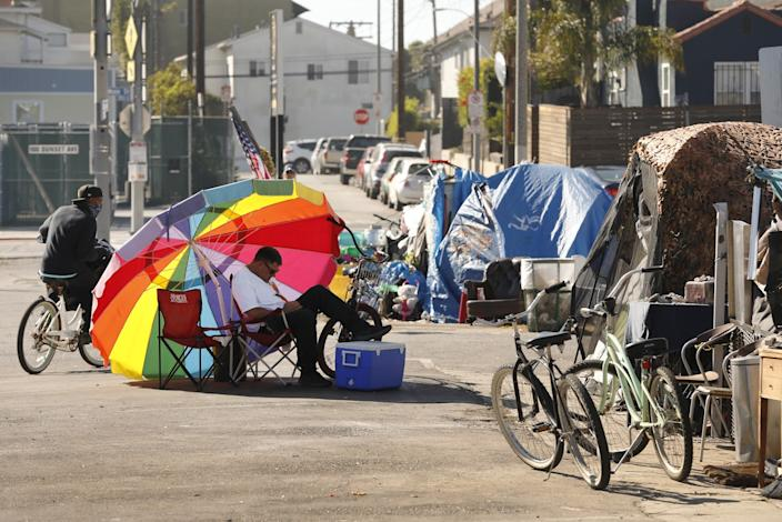 An umbrella shades Richard Thompson as he camps out with others in a Venice parking lot