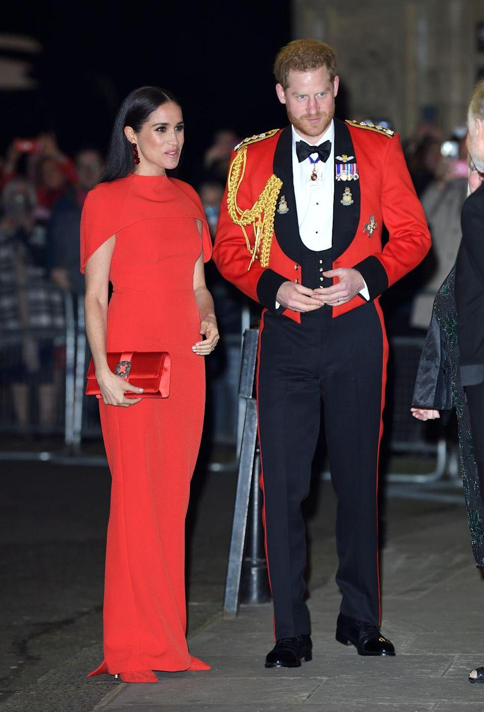 """<p><a href=""""https://www.townandcountrymag.com/society/tradition/a31262662/meghan-markle-red-gown-mountbatten-music-festival-photos/"""" rel=""""nofollow noopener"""" target=""""_blank"""" data-ylk=""""slk:Meghan attended the Mountbatten Music Festival alongside Prince Harry"""" class=""""link rapid-noclick-resp"""">Meghan attended the Mountbatten Music Festival alongside Prince Harry</a>, wearing a chic all-red look. The dress was reportedly from Safiyaa, which the Duchess wore with Aquazzura shoes, a Manolo Blahnik clutch, and Simone Rocha earrings. </p>"""