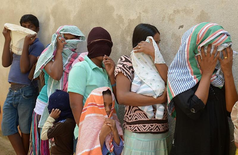 Sri Lankan asylum seekers sent back by Australia queue outside the magistrate's court in the southern port district of Galle on July 8, 2014 (AFP Photo/Lakruwan Wanniarachchi)