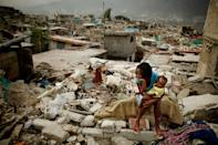 <p>Sherider Anilus, 28, and her daughter, 9-month-old Monica, sit on the spot where her home collapsed during the Jan. 12 earthquake in the Fort National neighborhood Feb. 26, 2010 in Port-au-Prince, Haiti. Living in a shack with her husband and two children, Anilus returned to Fort National from a tent camp in downtown Port-au-Prince so to escape the flash flooding that happens when it rains. (Photo: Chip Somodevilla/Getty Images) </p>