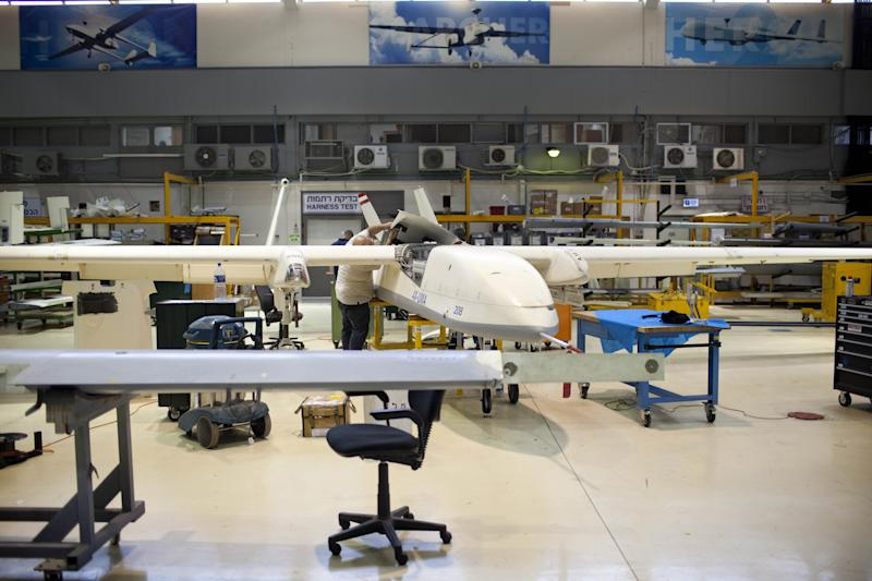 In this picture taken on Monday, May 28, 2013, Israel Aerospace Industries employees work on drones in a hangar, near Tel Aviv. In an expansive hangar in central Israel, workers toil on one of the world's most contentious aircraft, fitting dozens of drones with advanced sensors, cameras and lasers before they are shipped to militaries worldwide. Whereas drones are criticized elsewhere for being morally and legally objectionable, in Israel they are a source of pride. Israel has emerged as the world's leading exporter of the aircraft, putting it in a key position as the industry grows worldwide. (AP Photo/Oded Balilty)
