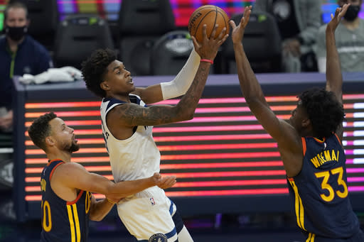 Minnesota Timberwolves forward Jaden McDaniels, middle, shoots between Golden State Warriors guard Stephen Curry, left, and center James Wiseman (33) during the first half of an NBA basketball game in San Francisco, Monday, Jan. 25, 2021. (AP Photo/Jeff Chiu)