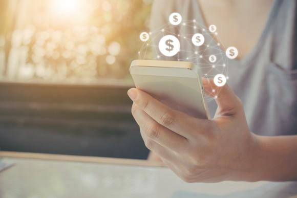 Money signs appear over a smartphone.