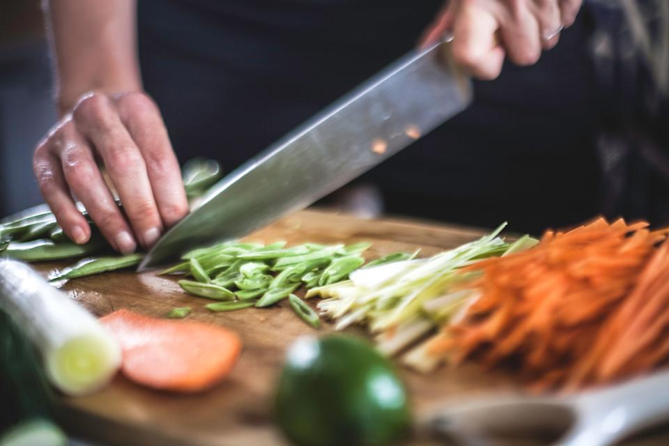 Close up shots of the cook's hands, finely slicing carrots, leeks and beans for a Korean dish.