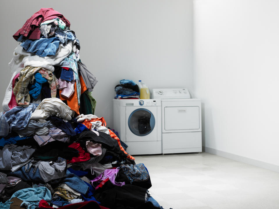 Laundry room with tall pile of clothes. (PHOTO: Getty Images)