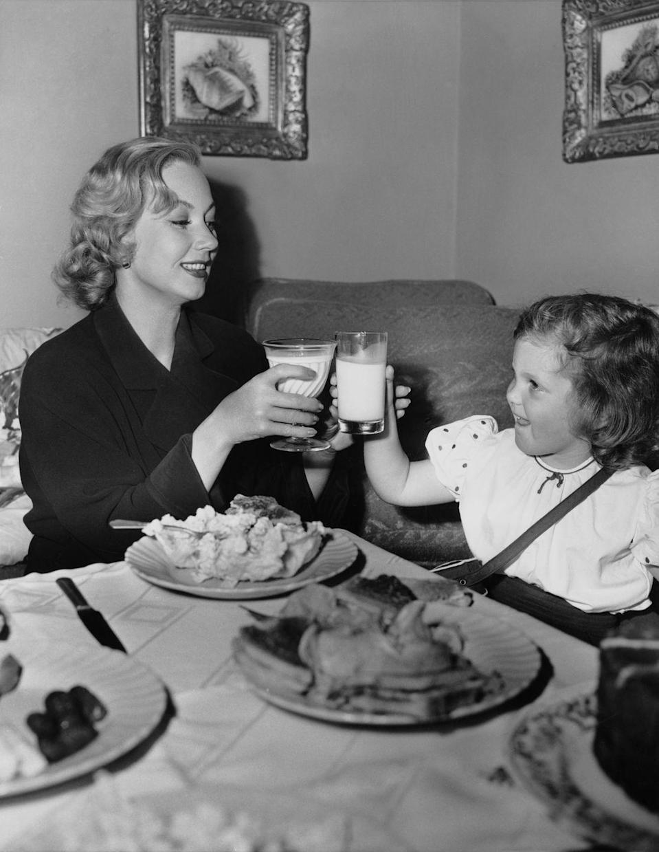 <p>The actress shares a milk toast with her daughter, Tisha Sterling, during a meal in her dressing room on the set of <em>Shadow on the Wall </em>in 1949. </p>