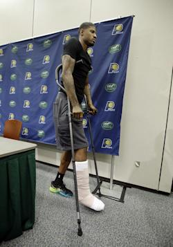 Paul George is using crutches to walk after breaking his right leg. (AP)