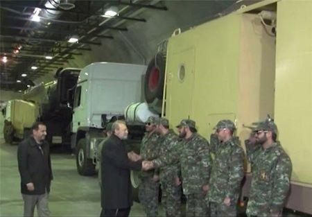 Iran's parliament speaker Ali Larijani shakes hands with a soldier as he inaugurates a new underground missile depot in this undated handout photo released January 5, 2016 by Farsnews.com. REUTERS/farsnews.com/Handout via Reuters